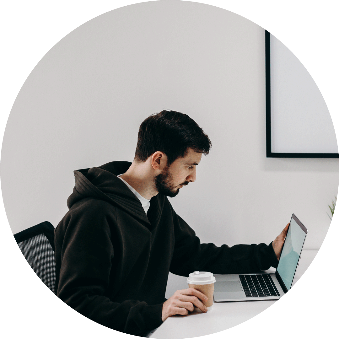 developer working on his laptop while holding a cup of coffee